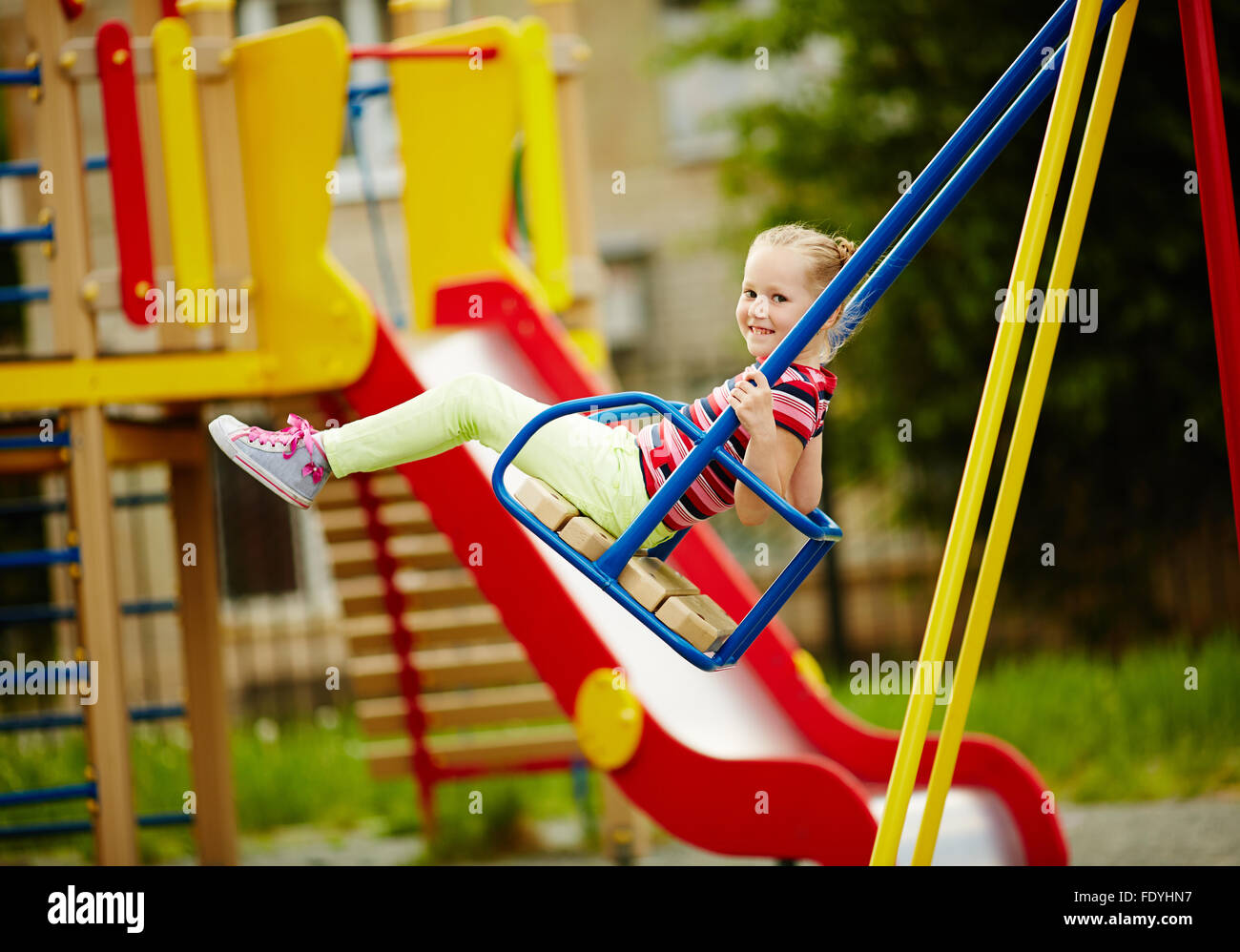 Little girl looking at camera while swinging on playground area - Stock Image