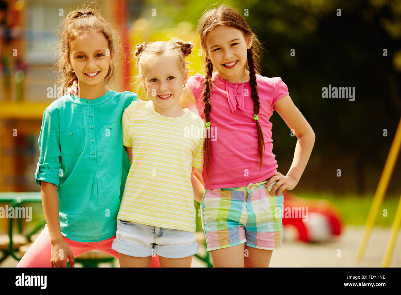 Adorable girls looking at camera with smiles outdoors - Stock Image