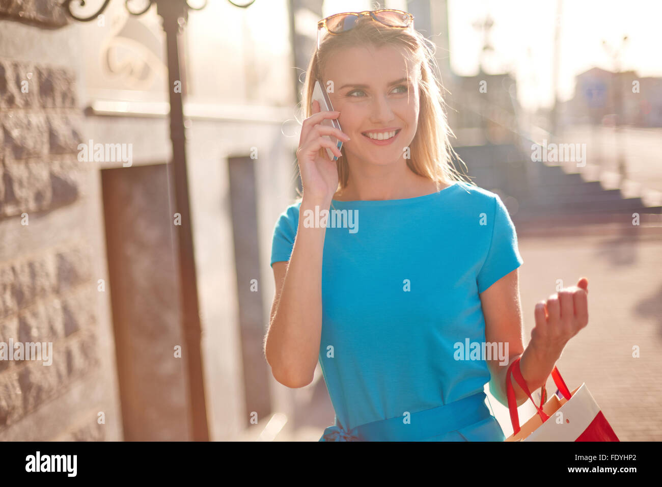 Young shopper with paperbags talking on the phone - Stock Image