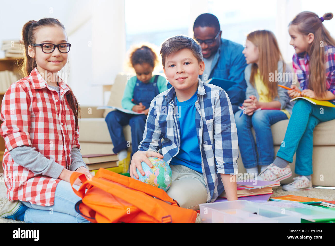 Little boy and girl looking at camera on background of teacher and other children - Stock Image