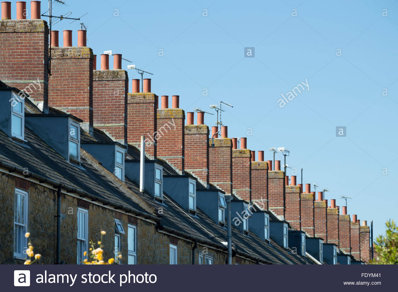 Roofs, chimneys and dormer windows of a long row of terraced houses, Sherborne, Dorset, England - Stock Image
