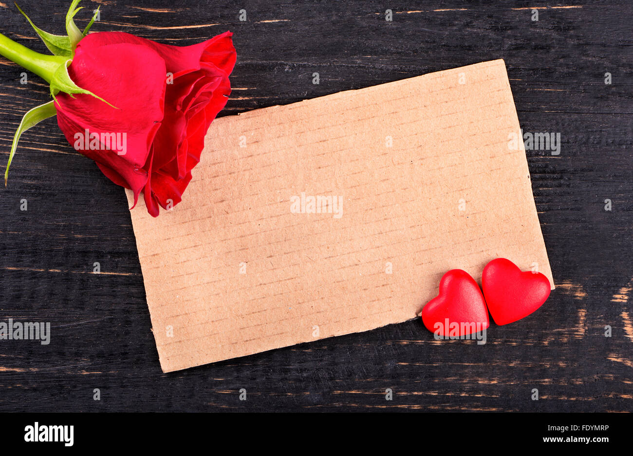 blank paper valentine card with two hearts and a red rose on wooden