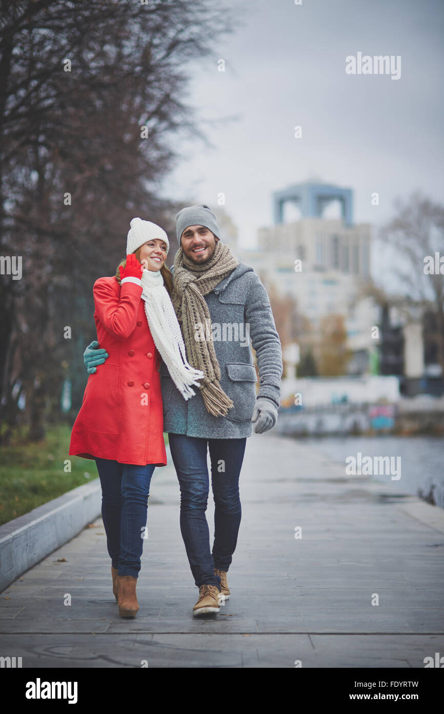 Happy dates in warm clothes spending day in urban environment - Stock Image