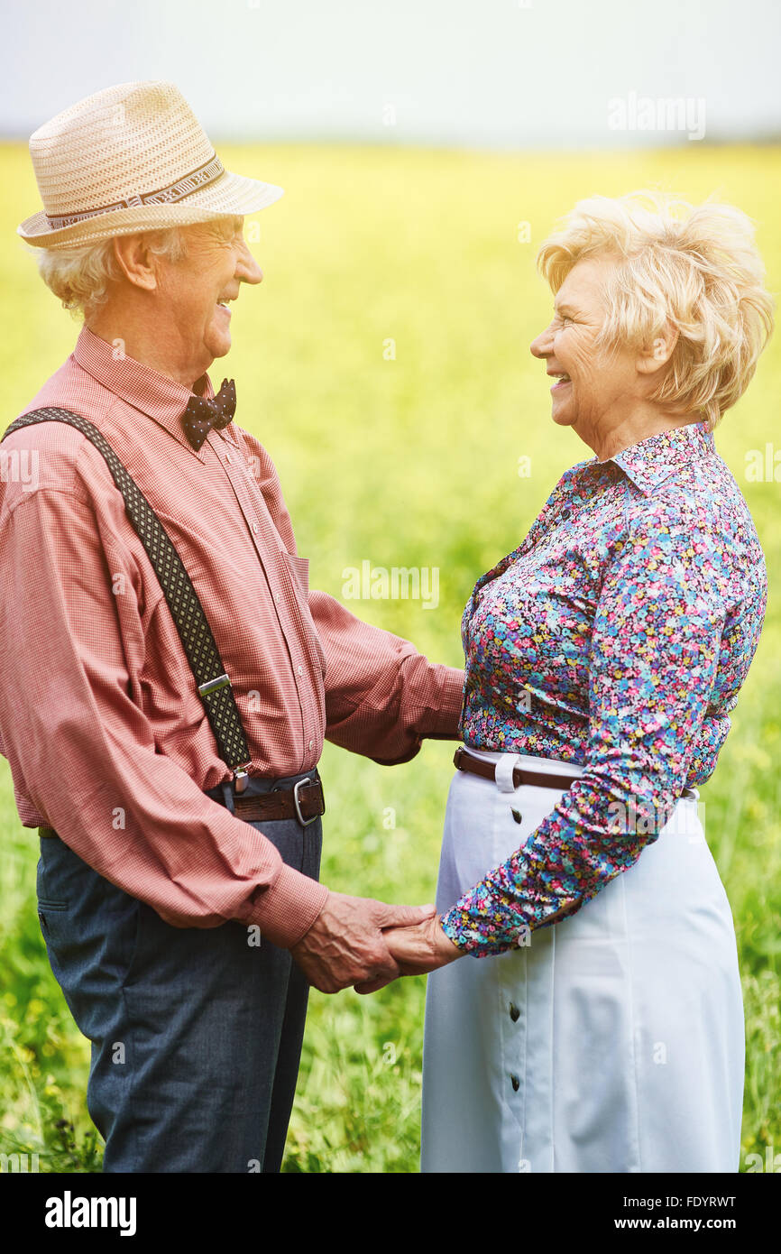 Cheerful seniors looking at one another in blooming meadow on summer day - Stock Image
