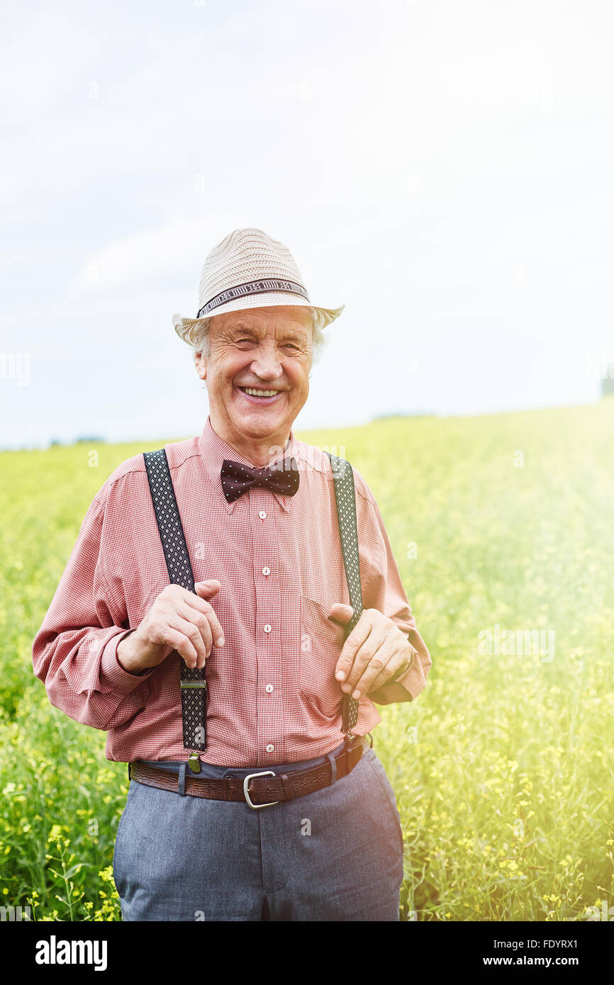 Happy well-dressed senior man looking at camera in meadow - Stock Image