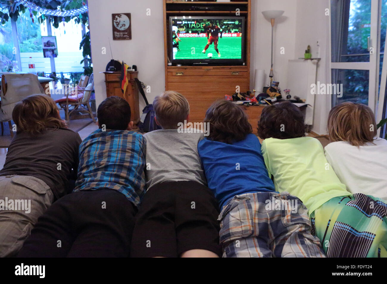 Berlin, Germany, boys look together a football game on television - Stock Image
