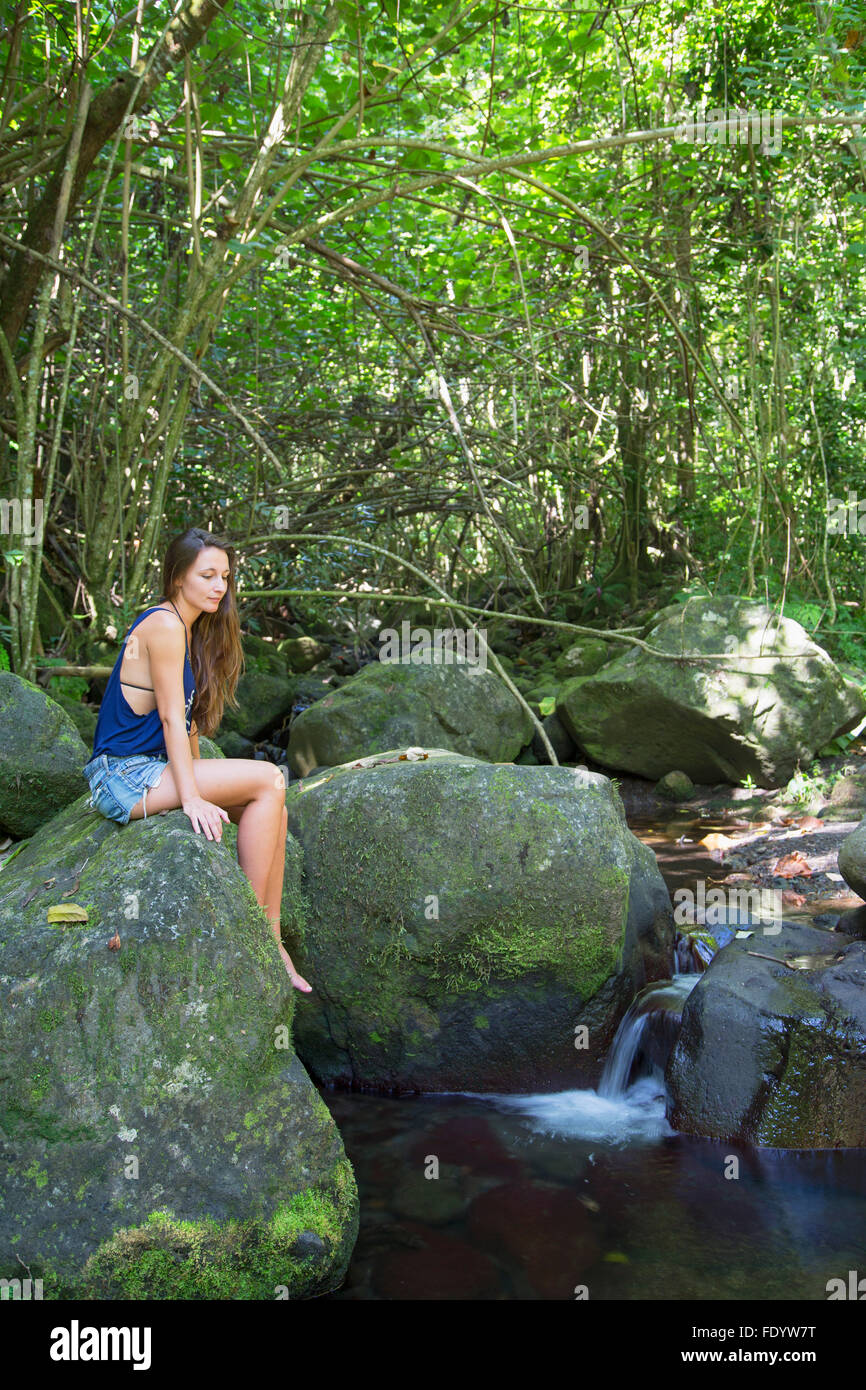 Woman sitting on rock in forest, Tahiti, French Polynesia - Stock Image