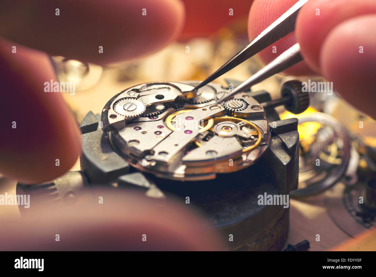 Working On A Mechanical Watch. A watch makers work top. The inside workings of a vintage mechanical watch. - Stock Image