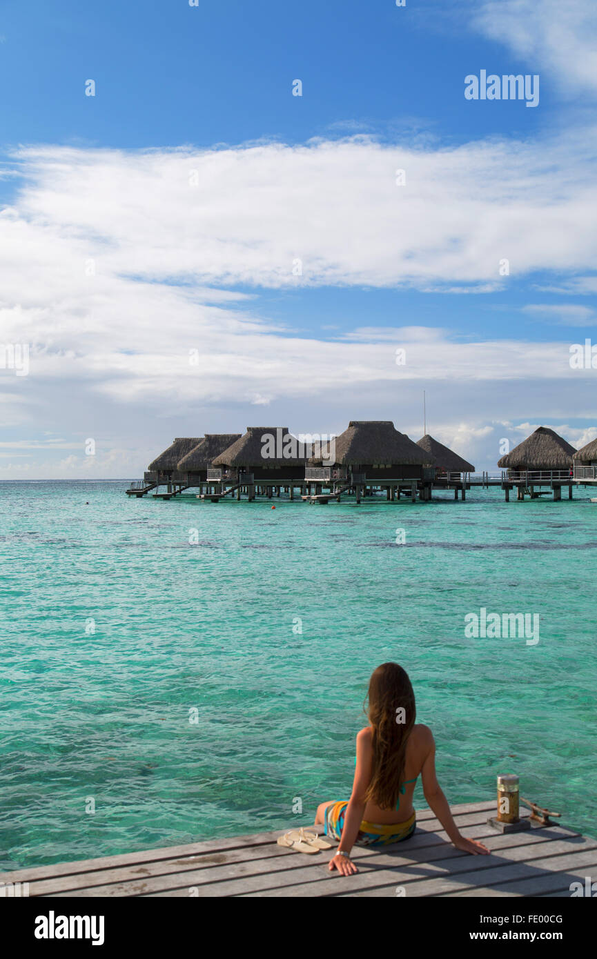 Woman sitting on jetty at Hilton Mo'orea Lagoon Resort Hotel, Moorea, Society Islands, French Polynesia - Stock Image