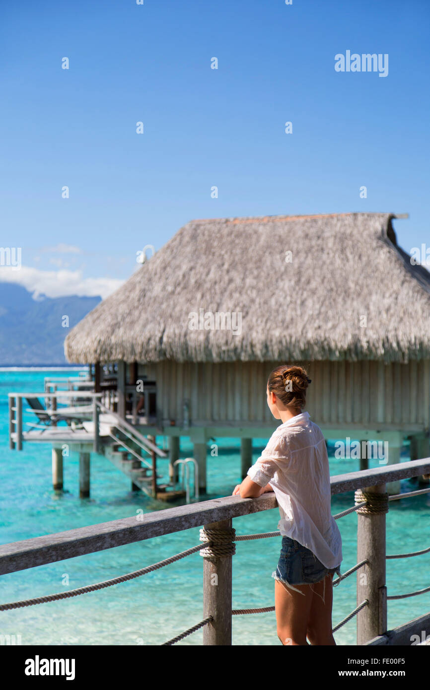 Woman on jetty of overwater bungalows of Sofitel Hotel, Moorea, Society Islands, French Polynesia - Stock Image