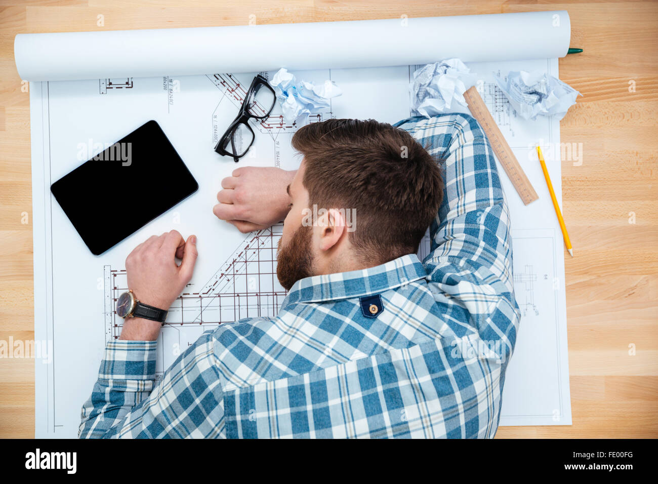 Top view of exhausted bearded young architect sleeping on workplace - Stock Image