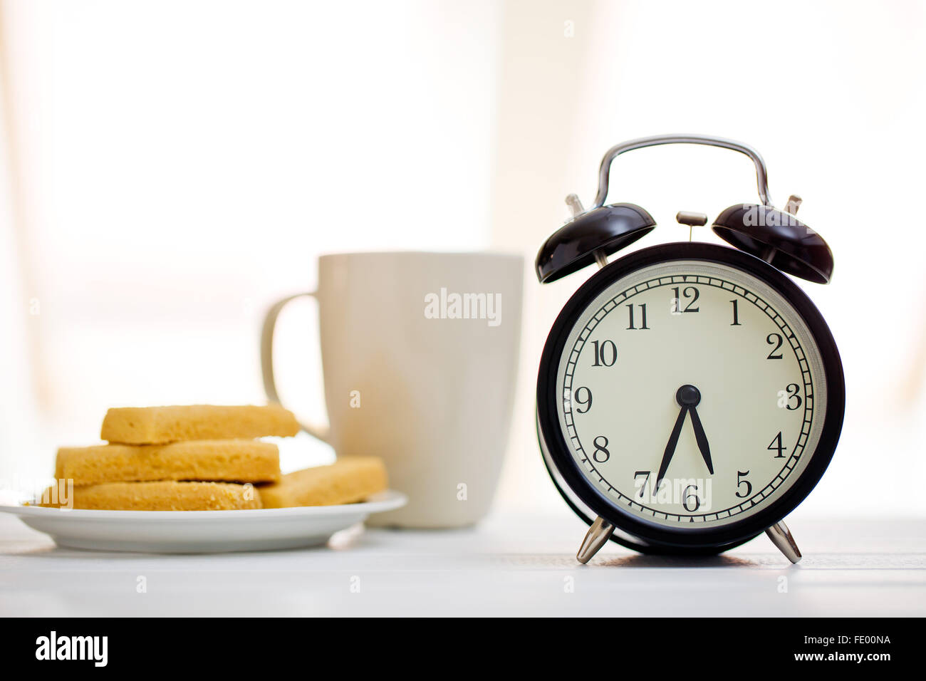alarm clock and breakfast on white table - Stock Image