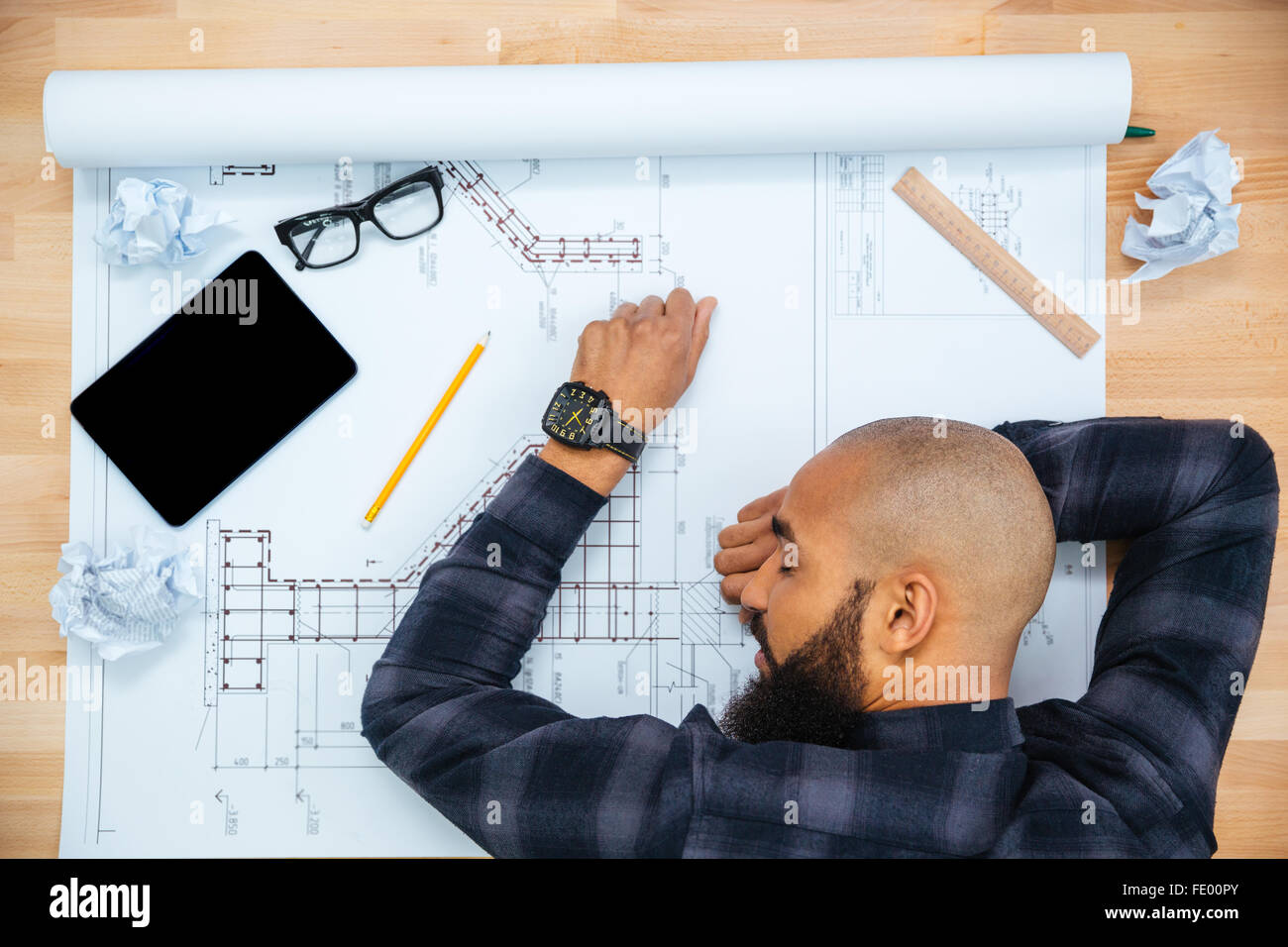 Young baldheaded african american young male designer with beard lying and sleeping on table with blueprint - Stock Image