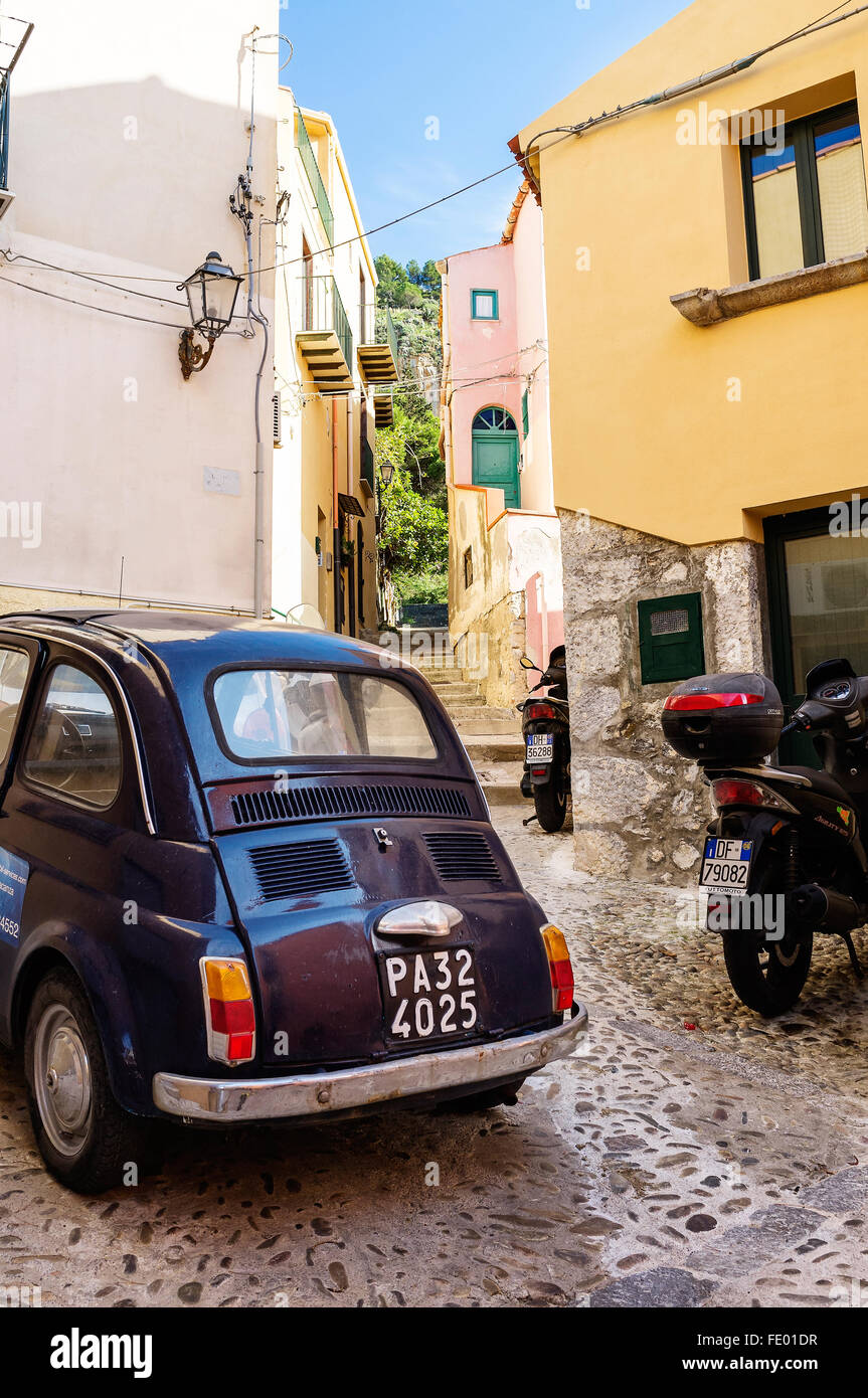 Vintage Fiat 500 and motorcycle parked in Cefalu city and comune in the Province of Palermo, Sicily, Italy - Stock Image