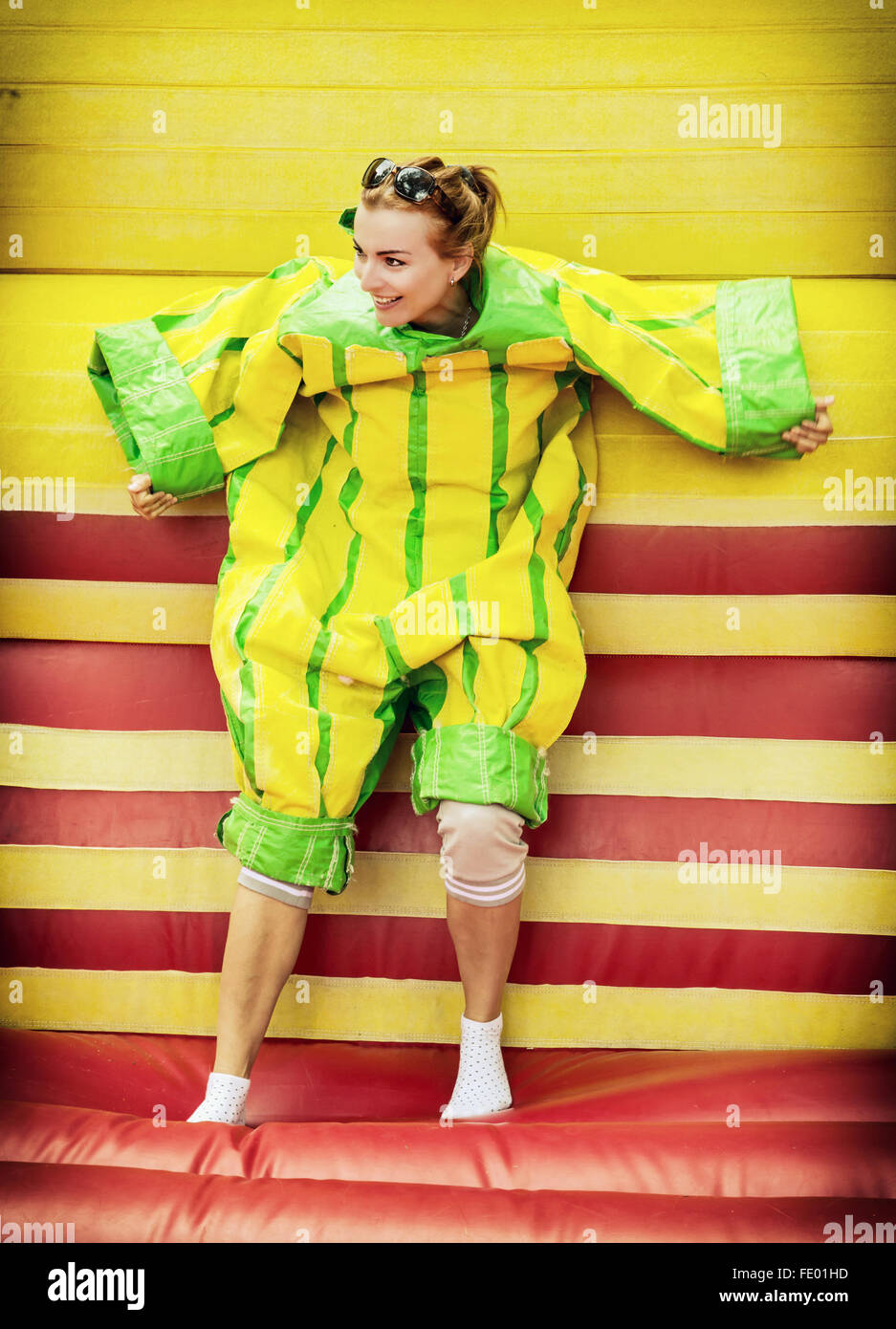 Joyful young woman in plastic dress in a bouncy castle imitates a fly on velcro wall. Inflatable attraction. Leisure Stock Photo