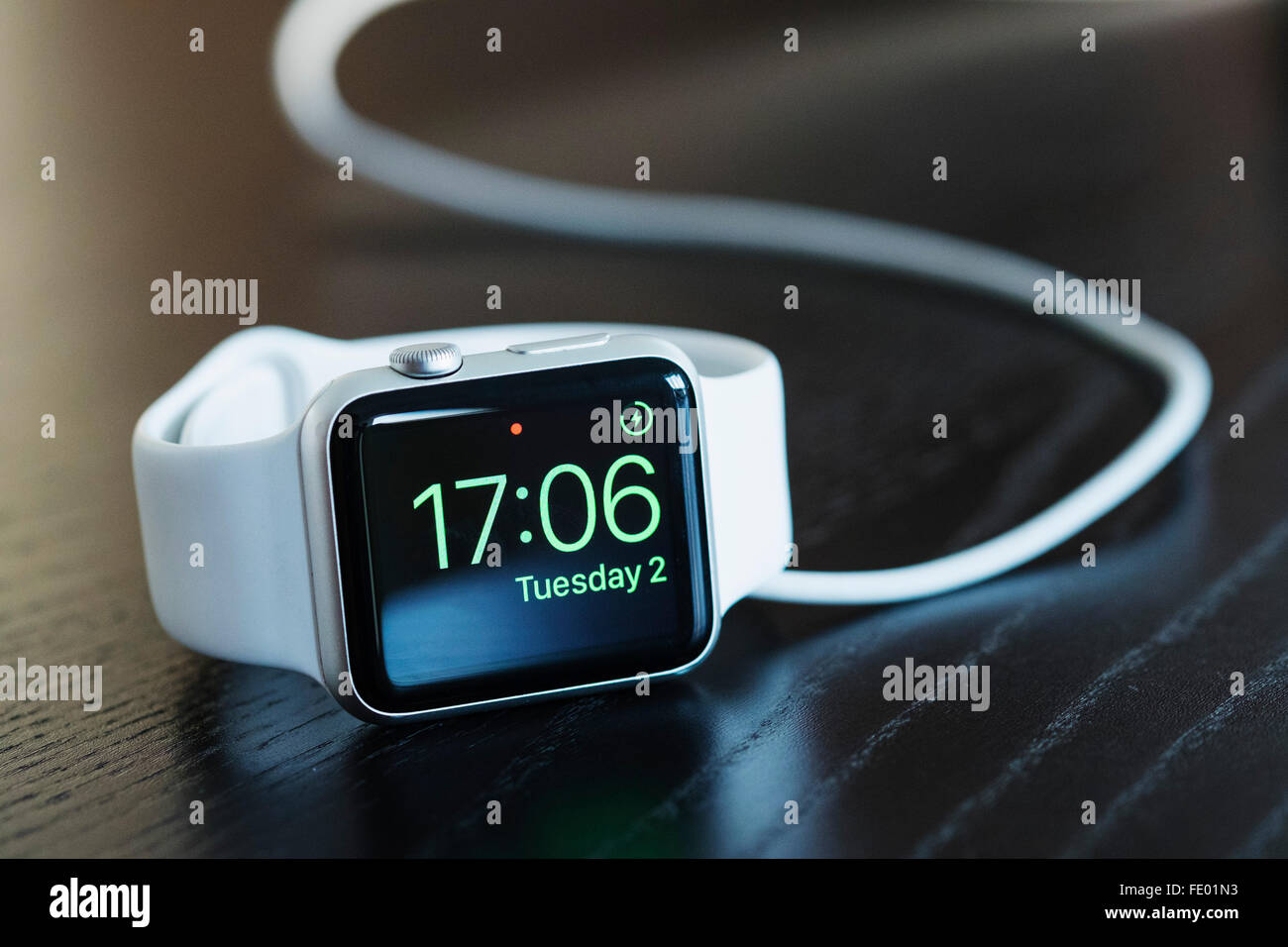 Apple watch with white strap charging and showing current time. - Stock Image