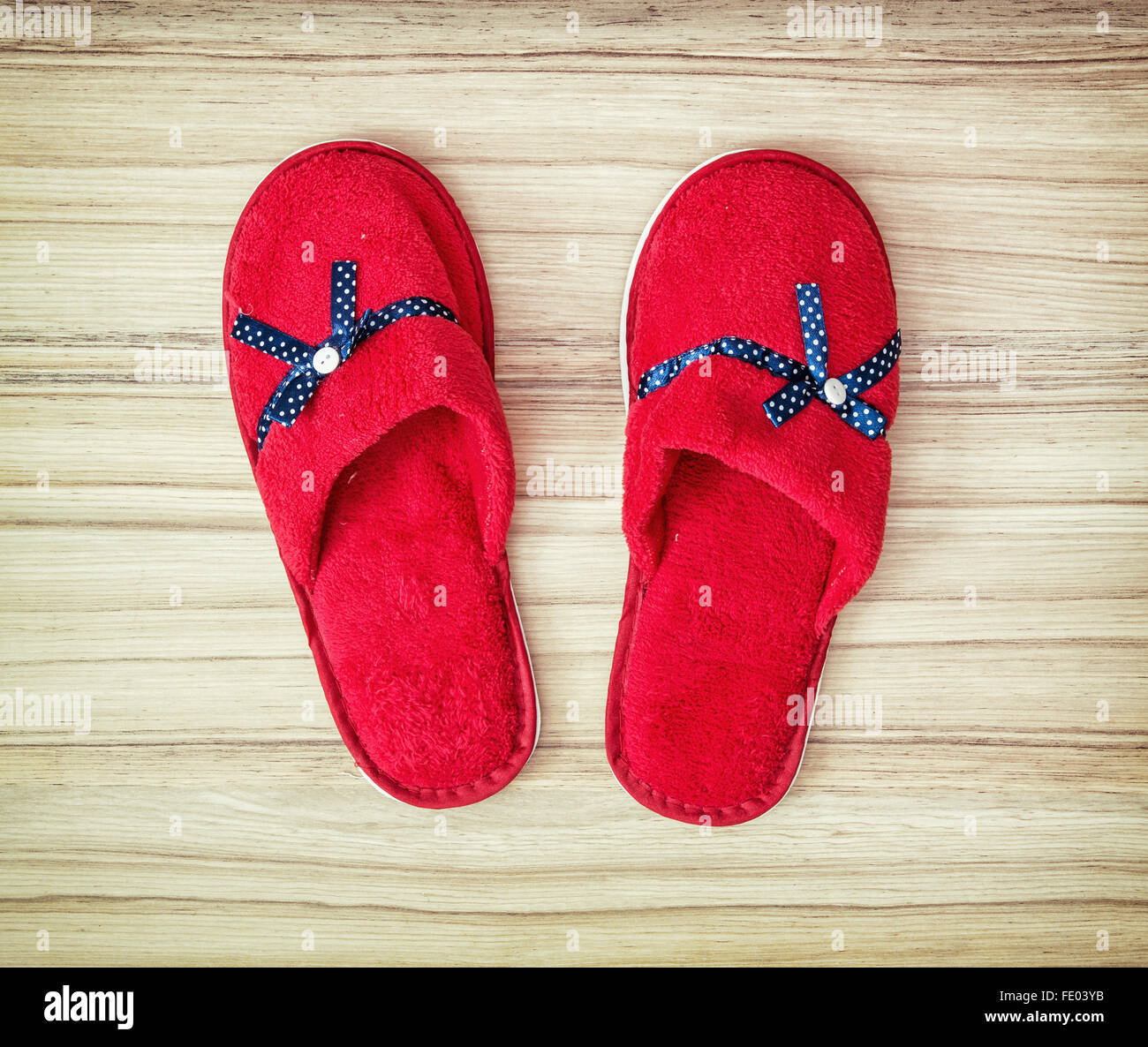 3e51aa82300 Red slippers with blue ribbon on the wooden background. Beauty and fashion.  Retro style.