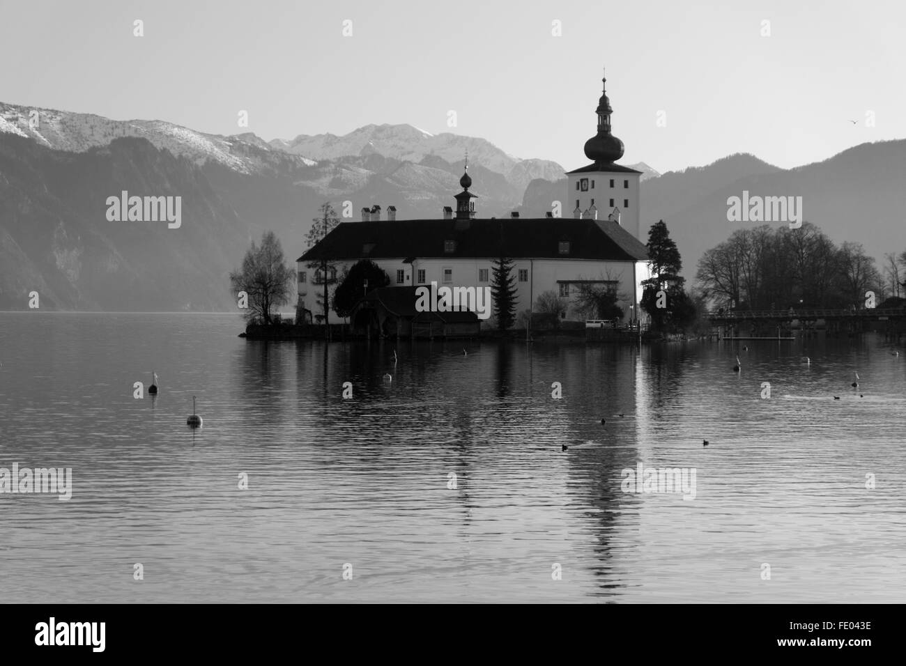 A black and white image of Schloss Ort in Gmunden, Austria, with snow covered mountains in the background - Stock Image