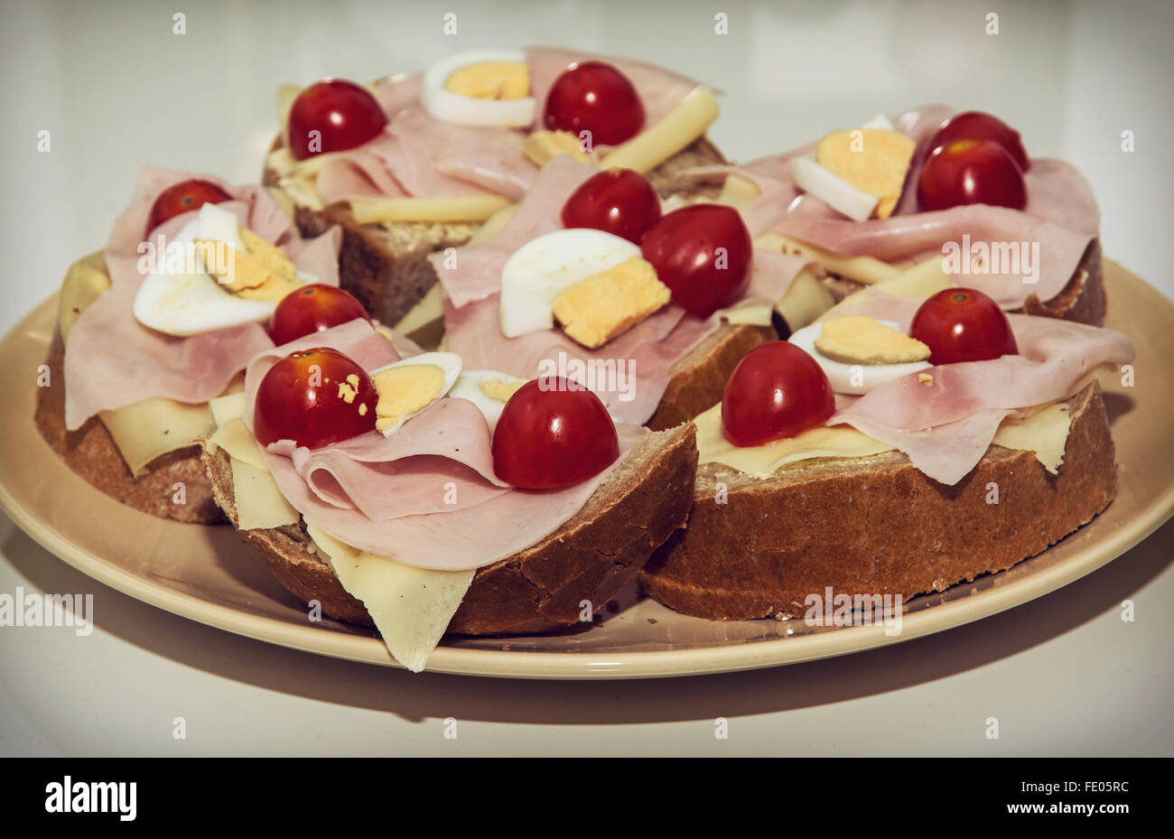 Tasty sandwiches with egg, cheese, ham and cherry tomatoes on the plate. Food theme. Stock Photo