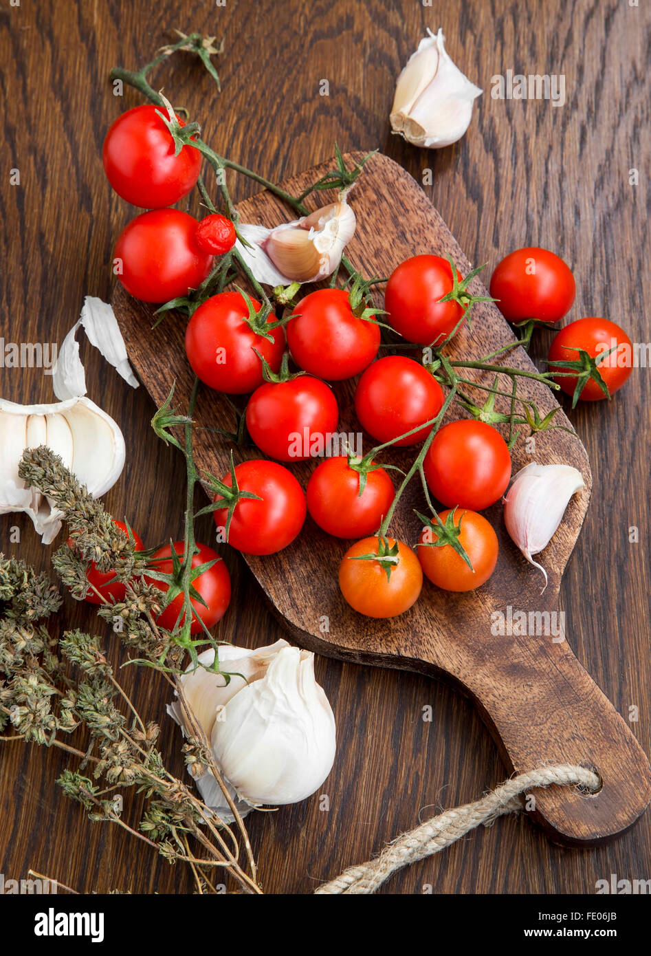 Organic cherry tomatoes with garlic and thyme herb on a wooden table - Stock Image