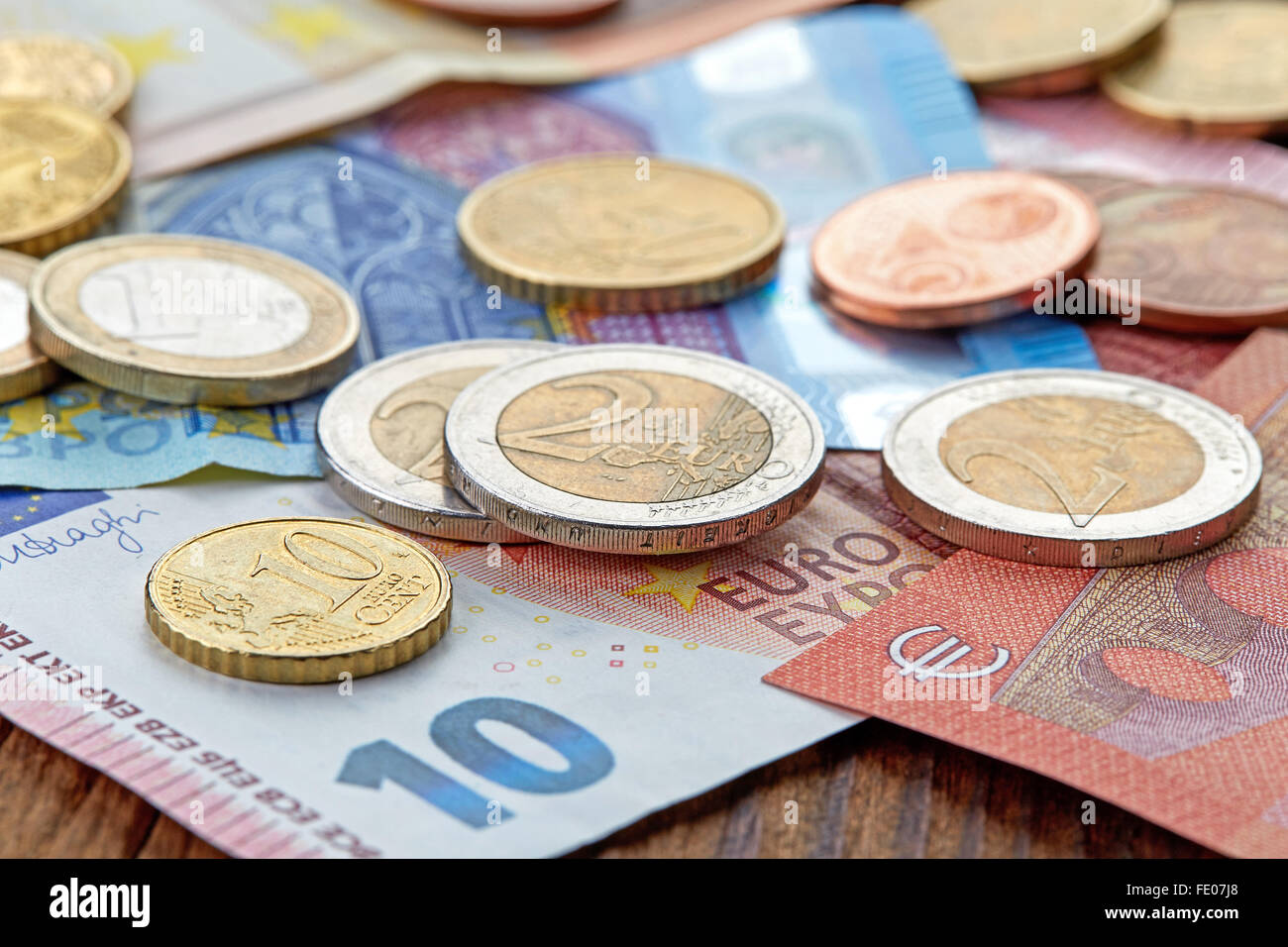 Money Euro banknotes and coins on wooden table - Stock Image