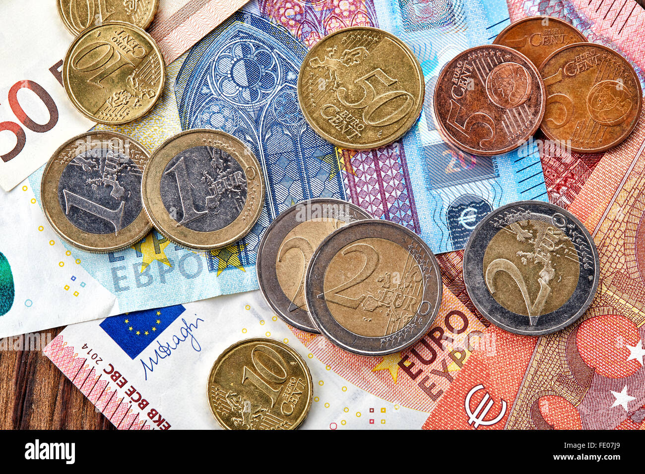 Money Euro banknotes and coins on wooden table, top view - Stock Image