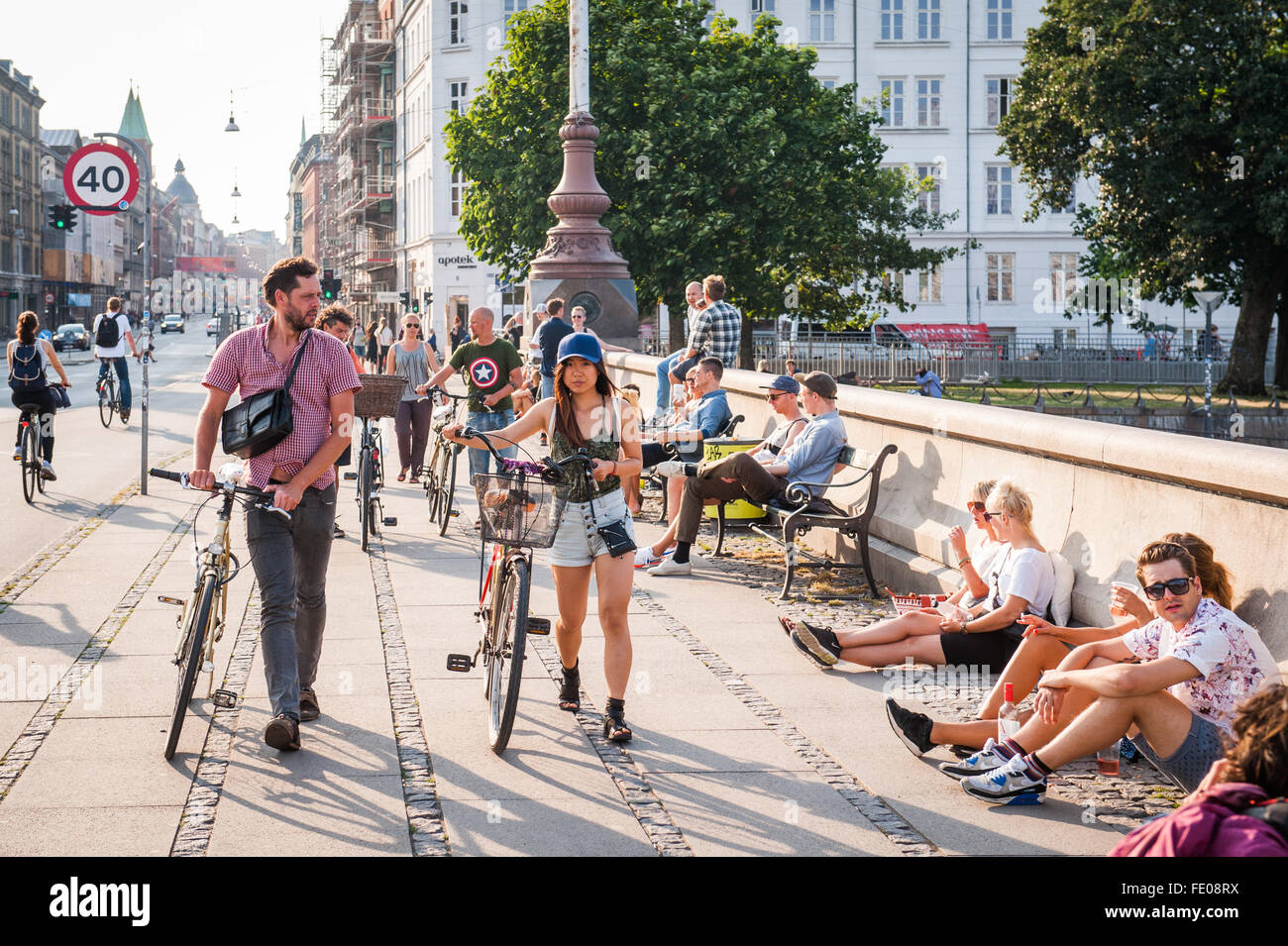 Young people hanging out in summer on Copenhagen's Dronning Louises Bro, in Norrebro area, Denmark - Stock Image
