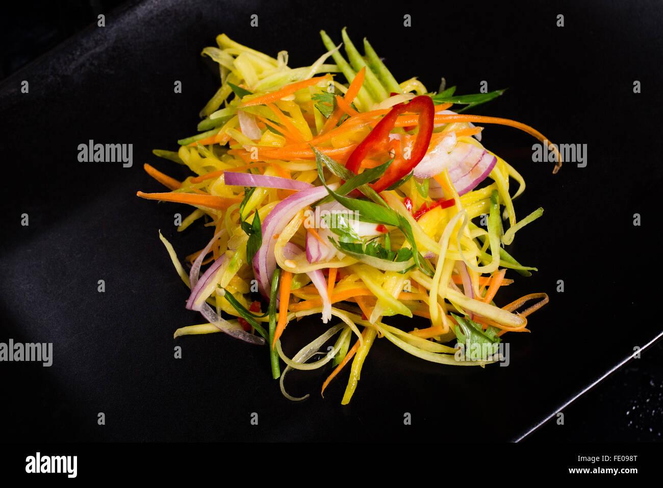 Mango Salat mit roten Zwiebeln, Chilli und Karotten , Asiatischer Fruchtsalat Asian Style Mango Salad on black plate Stock Photo