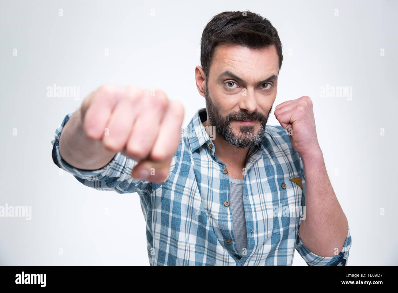 Handsome man punching with fist at camera isolated on a white background - Stock Image