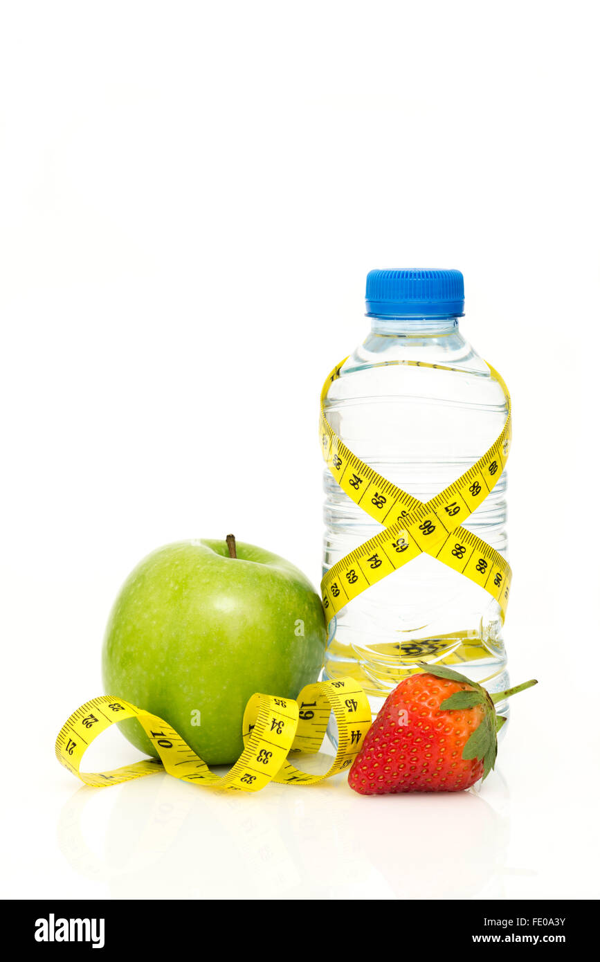 Water bottle wrapped in yellow metric tape measure with green apple and strawberry isolated on white background - Stock Image