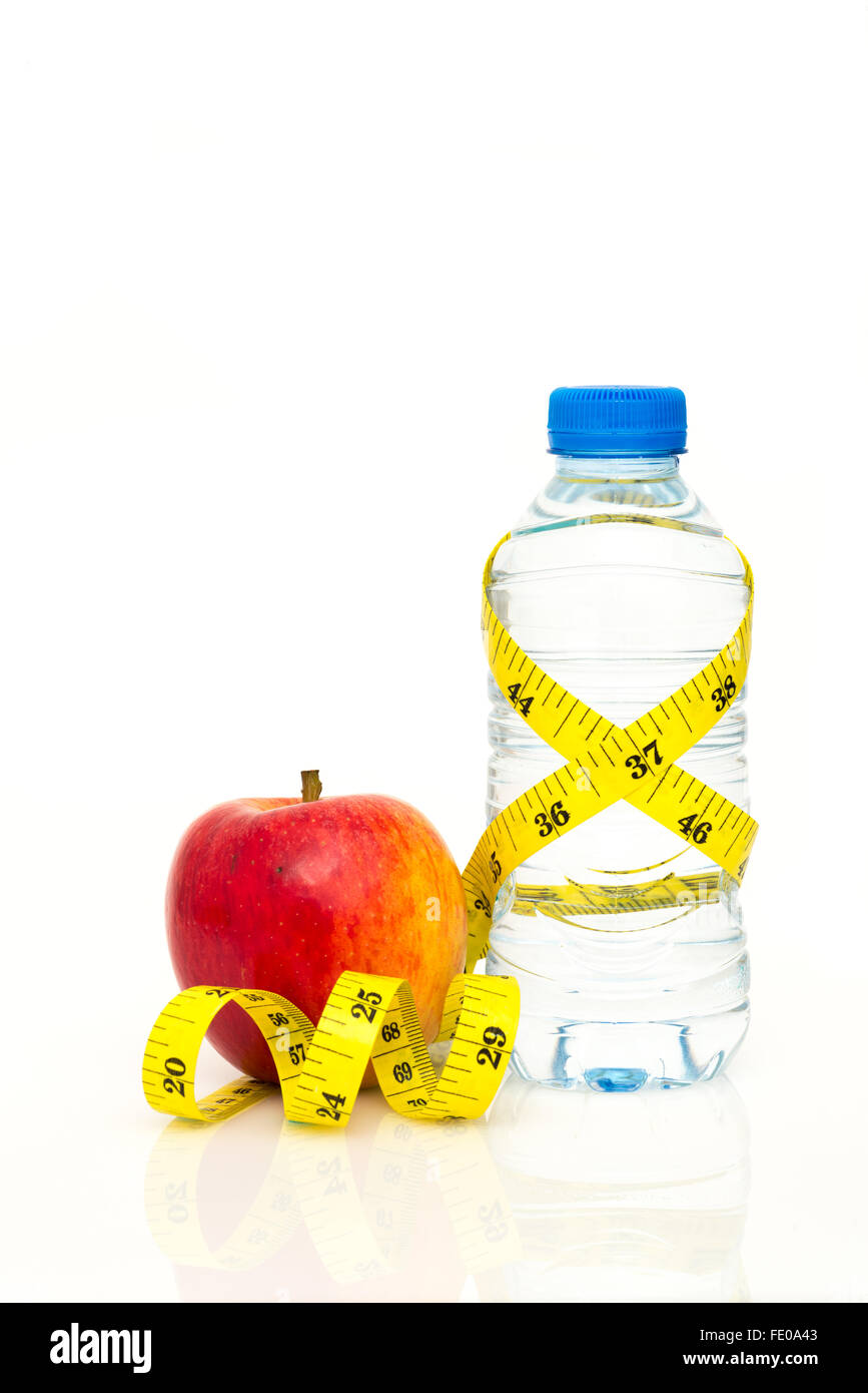 Water bottle wrapped in yellow imperial tape measure with red apple isolated on white background with copy space - Stock Image