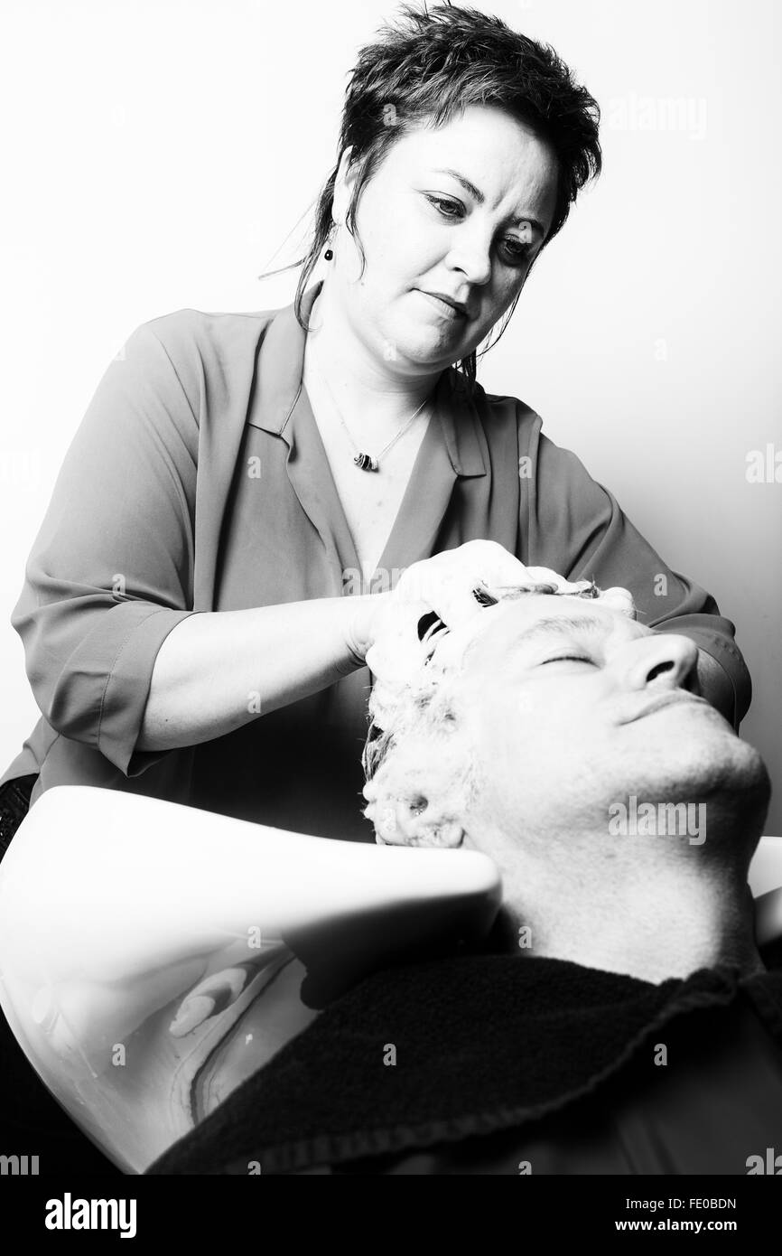 Close up of face of man is getting a hairwash by a hairdresser, with relaxation. The beautician is making foam from - Stock Image