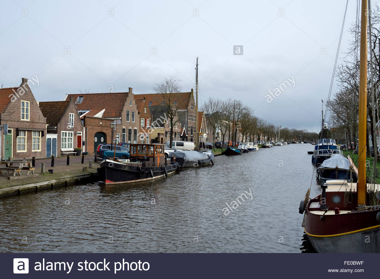 Boats are moored in the Nieuwehaven canal, by the old town section of Edam, province of North Holland, Netherlands. - Stock Image