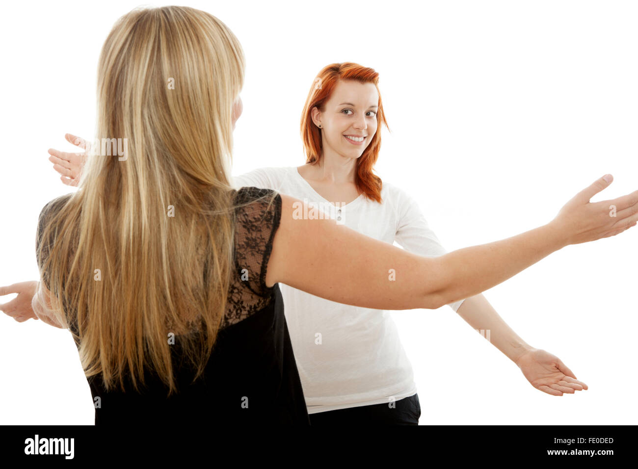 young beautiful red and blond haired girls in front of white background - Stock Image