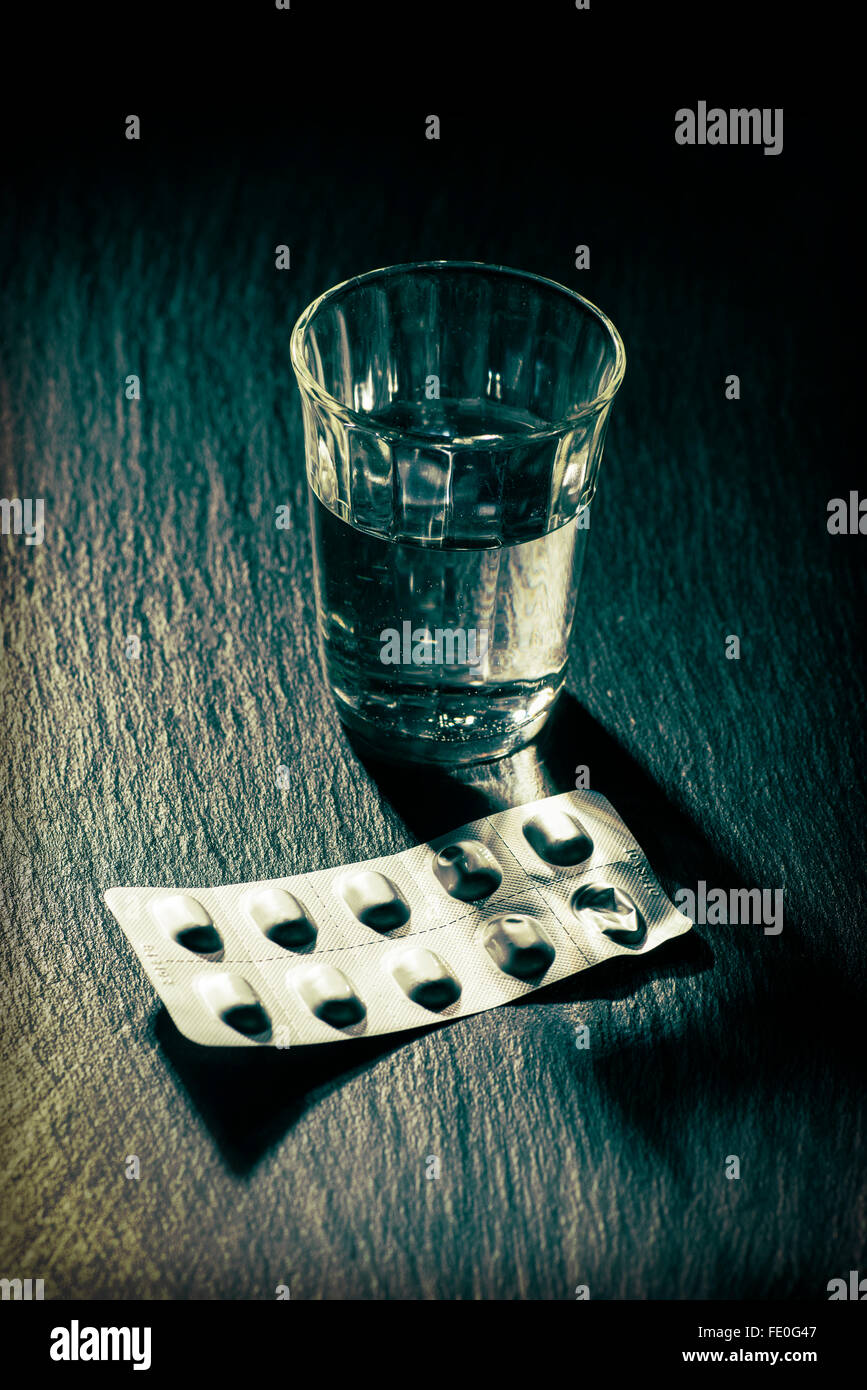 A glass of water and a blister with tablets - Stock Image