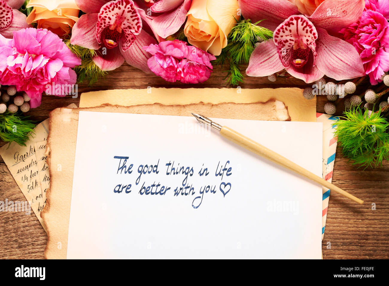 Floral arrangement with orchids, roses and handwritten words on vintage paper. - Stock Image