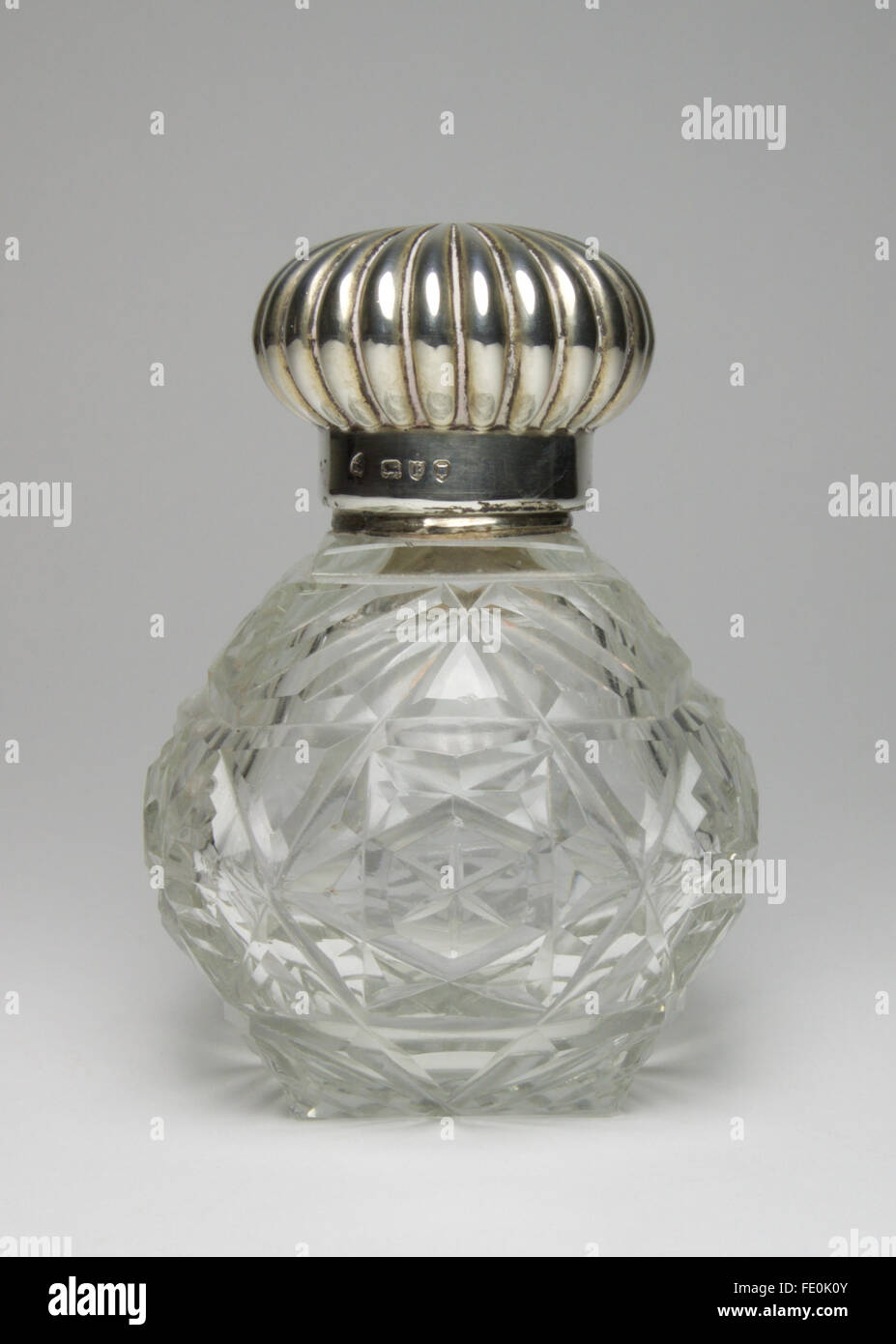 Beautiful antique 1892 silver topped cut glass perfume bottle. The gadrooned screw top reveals a small faceted glass - Stock Image