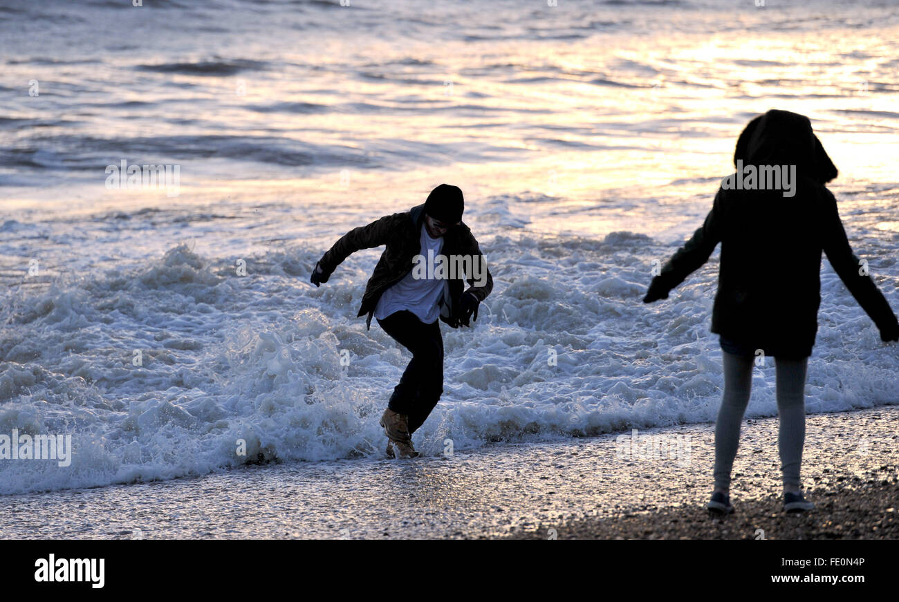 Brighton, UK. 3rd February, 2016. UK Weather: A young man enjoys dodging the waves at sunset on Brighton after a - Stock Image
