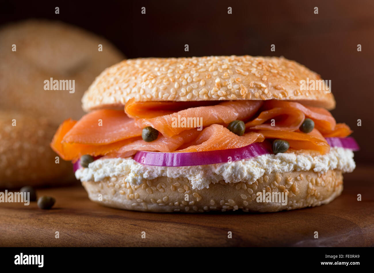 A delicious homemade sesame seed bagel with smoked salmon, whipped cream cheese, red onion, and capers. - Stock Image