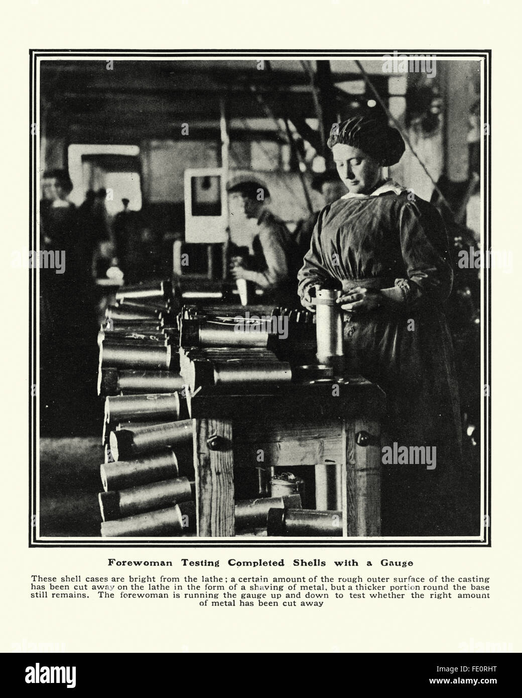 Woman in a first world war munitions factory testing completed shells. - Stock Image