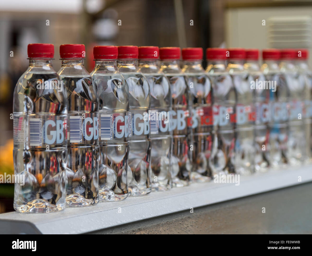 Line of plastic water bottles displayed in the Covered Market, Cambridge - Stock Image