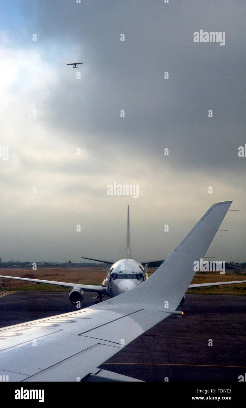 Airplanes at airport and in sky - Stock Image