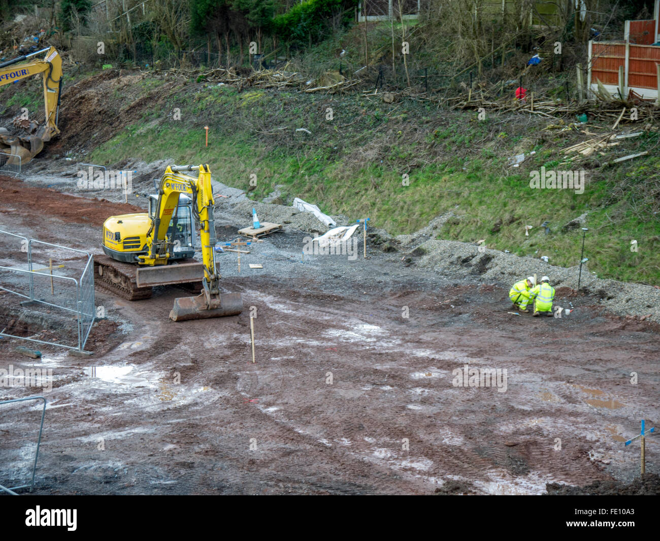 Diggers working with men in safety jackets and helmets placing wooden markers. - Stock Image