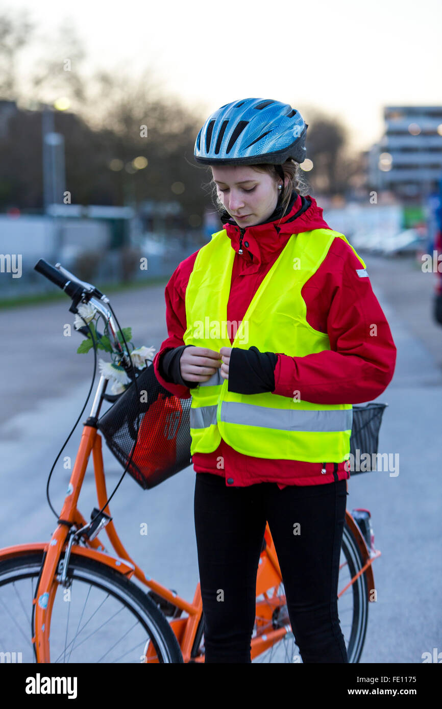 Cyclist put on safety clothing, bike helmet and reflecting vest for bike safety, good visibility at night in traffic Stock Photo