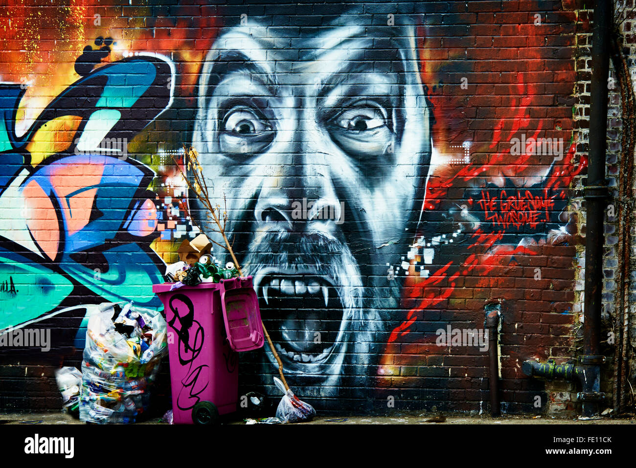 Highly colourful Graffiti design and face  with real life rubbish bins - Stock Image