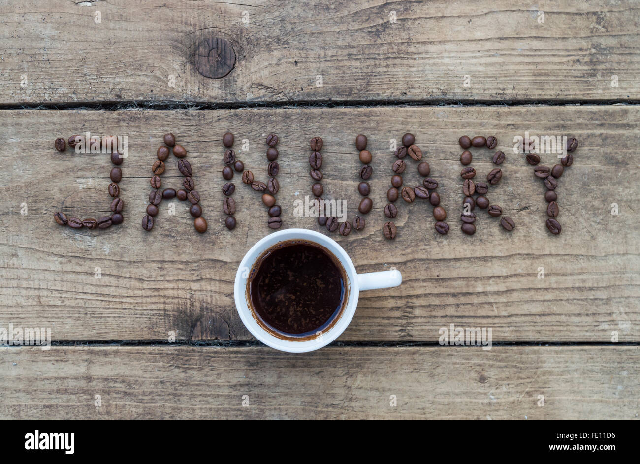 Cup of coffee on wooden background and January coffee beans Stock Photo