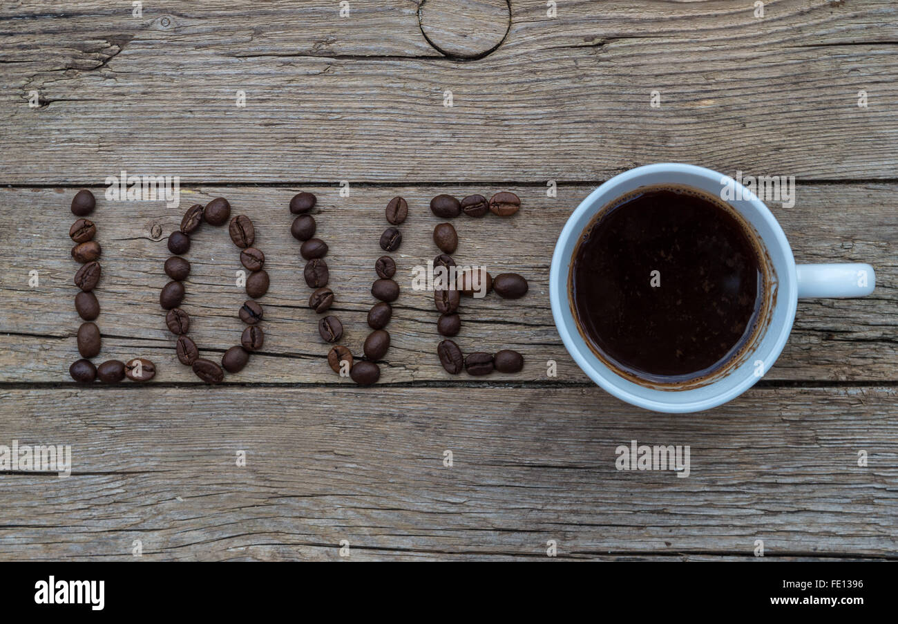 Cup of coffee on wooden background and LOVE coffee beans Stock Photo