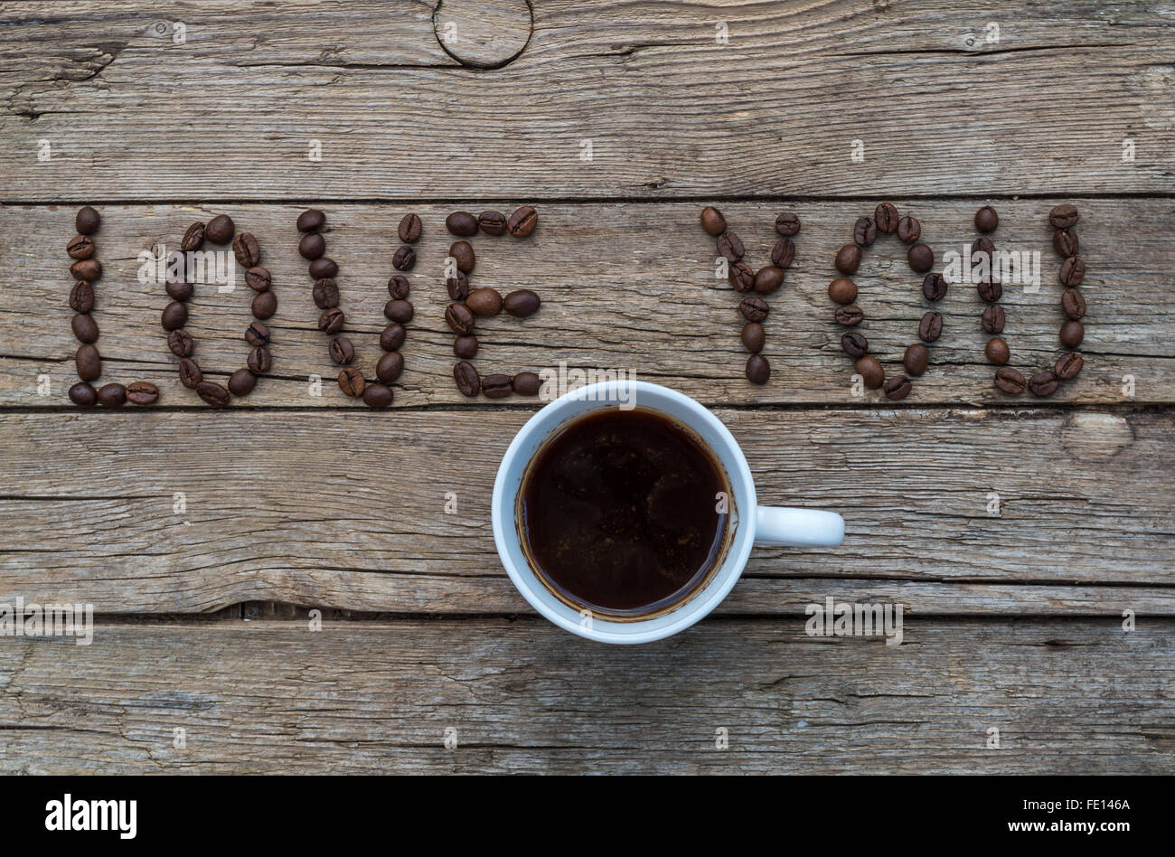 Cup of coffee on wooden background and LOVE YOU coffee beans Stock Photo