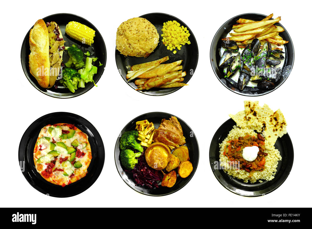 Different Meals On Black Plates Photographed Against A White Stock Photo Alamy