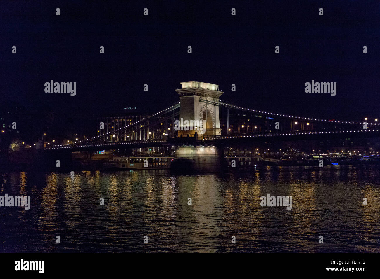 Chain Bridge over the Danube River Budapest Hungary, at night with the sparkling lights reflecting in the river - Stock Image